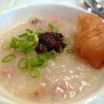 Congee with grilled prawns, poached egg, scallion, and Chinese doughnut