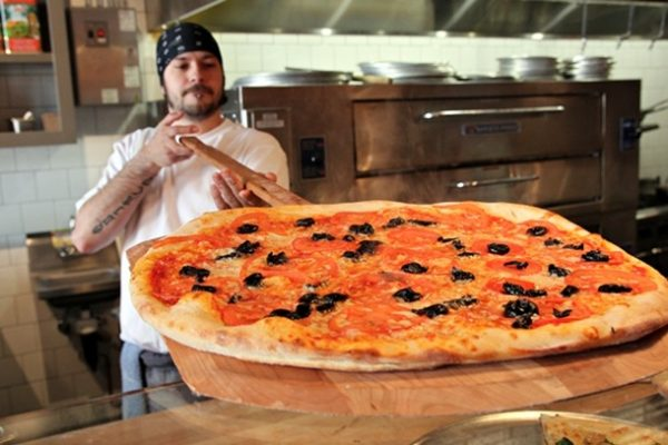 Fresh from the oven, Keiji serves up the day's special pizza: fresh tomato and oil-cured olives.