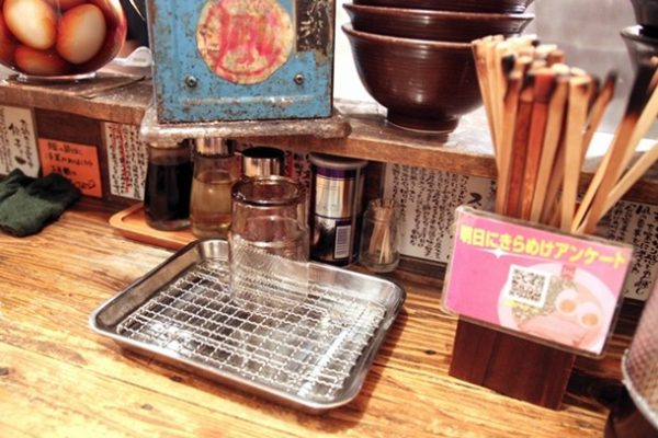When you're called back up, you'll get one of the ten counter seats. If you understand Japanese, there's all kinds of information about the food that you can read. On the counter you'll find everything you need for your meal, including chopsticks, water, soy sauce, vinegar, spice powder, and toothpicks. Ask and you can get sansho rayu. This chili oil, spiked with numbing and earthy sansho peppercorns, will be a good complement to the bitter ramen broth.