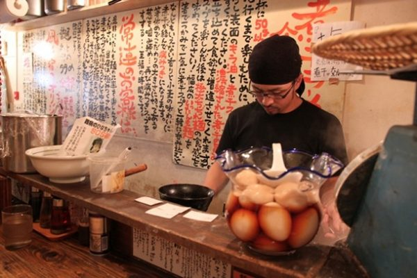 Next to the scale is a big bowl full of perfectly cooked eggs. Behind, the chef prepares an order. The wall describes how the ramen is made and gives information about how to best enjoy the ramen.