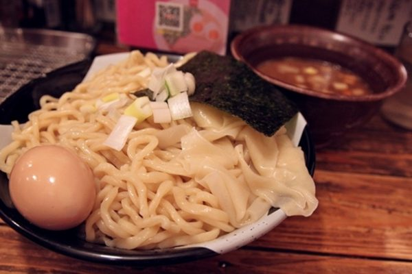 Here is an order of tsukemen, with an egg (900 yen, or about $11.20). I ordered 400 grams. Note that, as with their hot ramen, there are actually two types of noodles. In addition to the thick round noodles, there's a small portion of wide, tagliatelle-type noodles that are starting to approach the size of lasagna sheets. Behind is the niboshi dipping sauce, which contains cubes of pork.