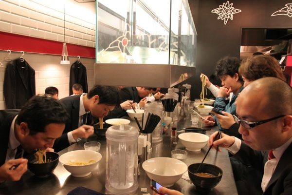 Salarymen slurping in unison at Honda, an up-and-coming ramen restaurant with an original location in a distant part of northern Tokyo. There are artistic bowls in the showcase.