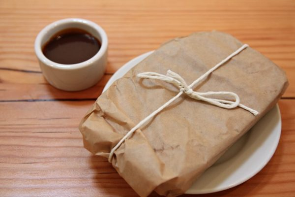 Presentation of the grilled chocolate sandwich ($7.50), wrapped in parchment paper with a side of salted caramel sauce.