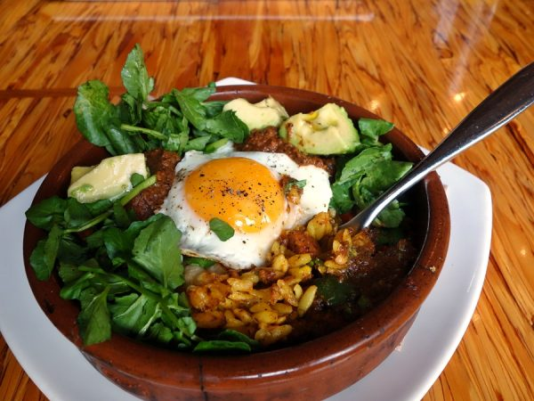 Cafe Medina's paella (baked egg, curried Orzo, Hungarian chorizo, zucchini, red pepper, roasted corn, Grano padano. Watercress, avocado, and tomato salad)