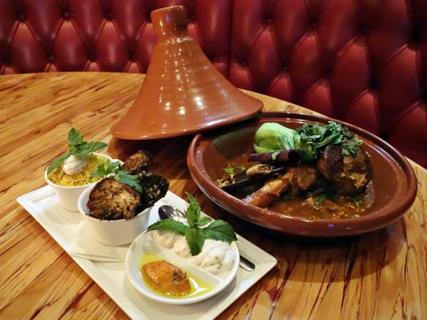 Chambar's tajine d'aziz à l'agneau: braised lamb shank with honey, figs, cinnamon & cilantro, served with cous cous, zalouk, harissa, and raita (fabulous flavors)