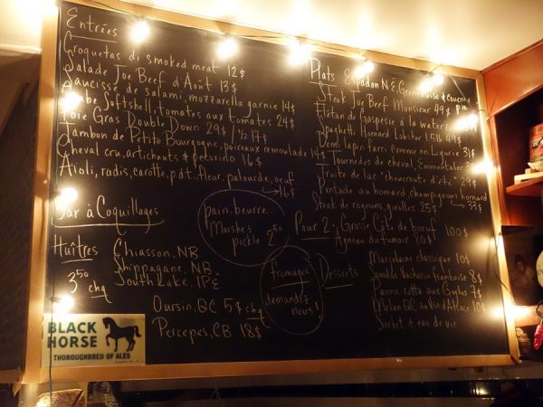 "The ""iconic"" blackboard menu at Joe Beef. Note the vintage Playboy magazine on the shelf, which contains lots of other curiosities."