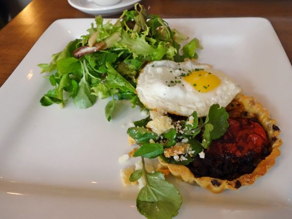 Roasted tomato brioche tart with gaeta olives, balsamic caramelized onions, baked chèvre, and sunny egg at Beast + Bottle