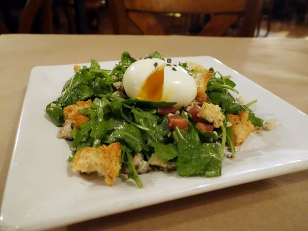 Spice's arugula salad with 6-minute egg, lardons, torn croutons, and scallion vinaigrette