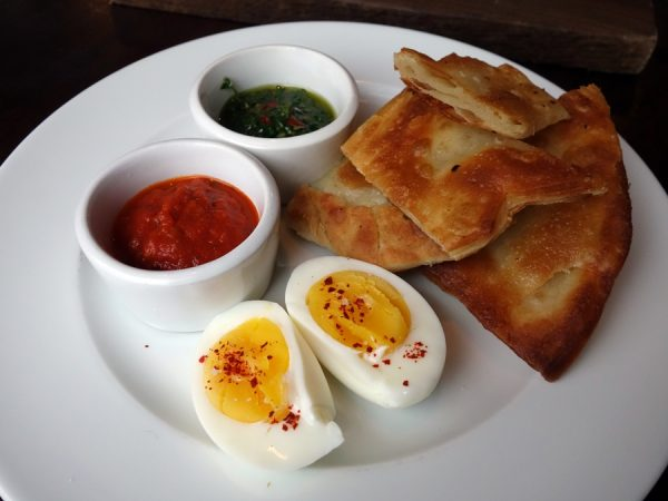 Cafe Castagna's malawich (a buttery bread to shatters with each bite) with tomato sauce, zhoug (a spicy herbal relish), and hard-boiled egg