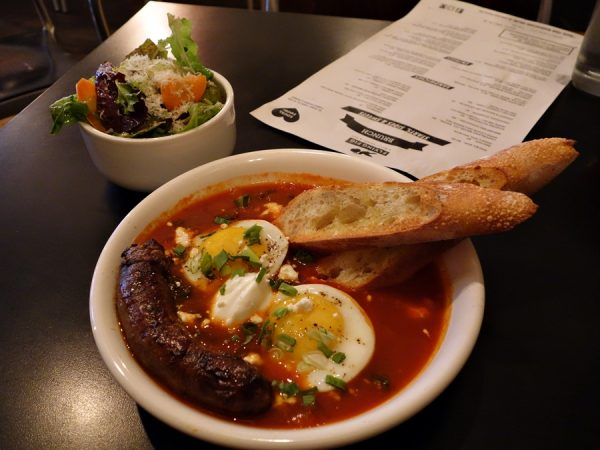 Flying Fig's shakshuka: North African tomato sauce baked with eggs, sweet & hot peppers, onions, and kale — topped with yogurt and feta. Plus that spicy lamb sausage and side salad.