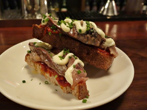 Espana's toast of smoked sardines, bravas sauce, and aioli