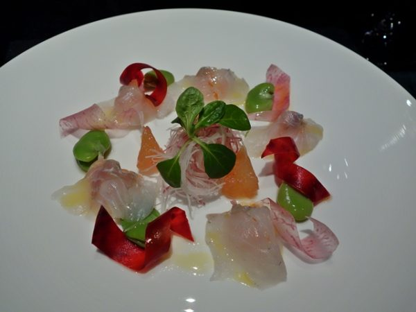 Suzuki no arai: The Japanese sea bass is cut like sashimi, then washed with ice water and lemon to tighten the fish. (Lemon takes out any smell and adds flavor). The plate has grapefruit pieces, grapefruit dressing, fava beans, and ribbons of Koshin daikon and beet.