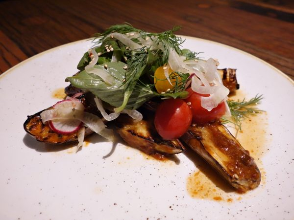 Grilled eggplant with fermented black bean vinaigrette, sesame, shallots, tomatoes, and herb salad