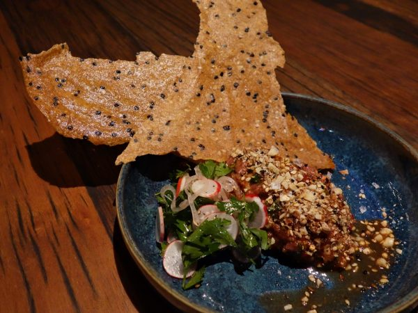 Anderson Ranch lamb tartare with cured lemon, rose petal harissa, radish, herbs, flatbread, and dukkah spice