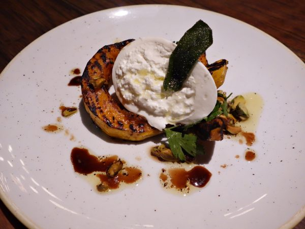 Grilled kuri squash with burrata, toasted pistachio oil, saba, sea salt, and parsley