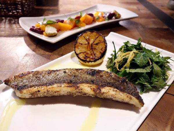 Sea bass with charred lemon and herbed greens (background: young beets with pistachio-crusted goat cheese and mandarin oranges) at Carson Kitchen